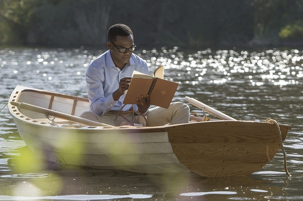Chidi reading on a boat