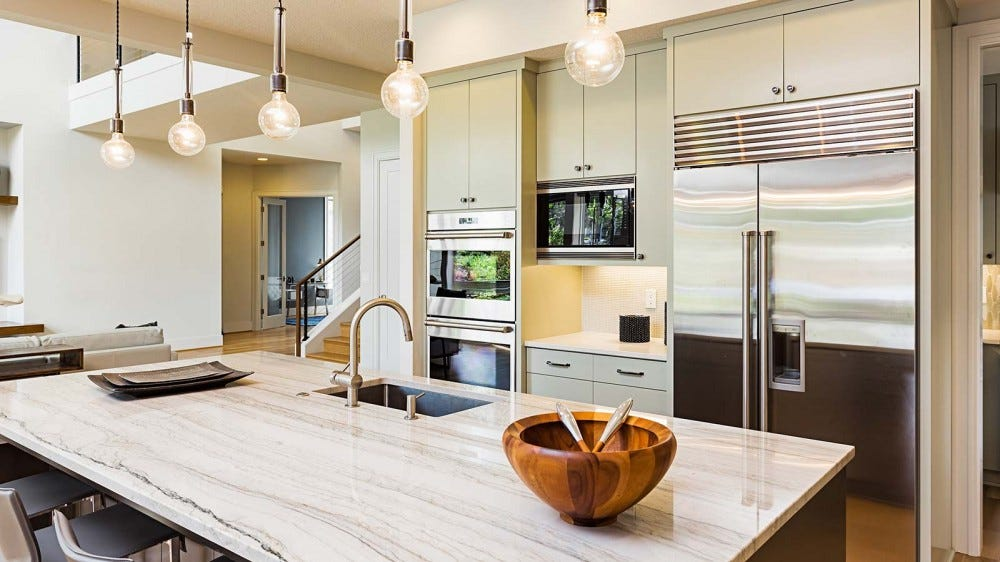 A beautiful modern kitchen with marble counters and high-end appliances.
