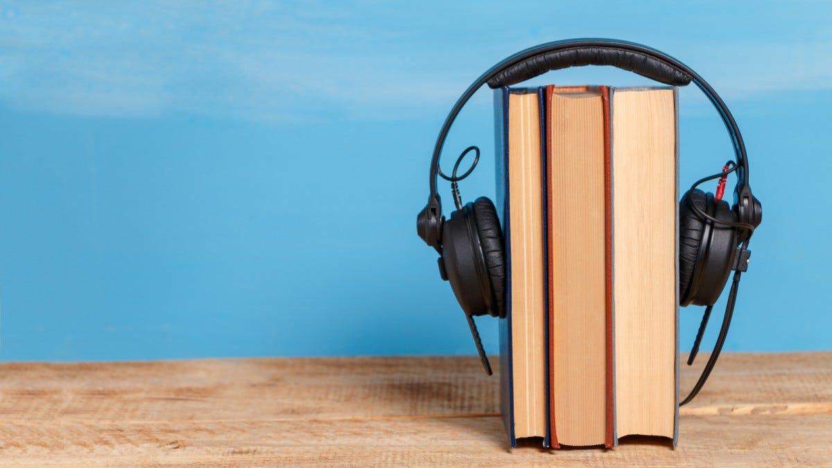 A pair of headphones around three books.
