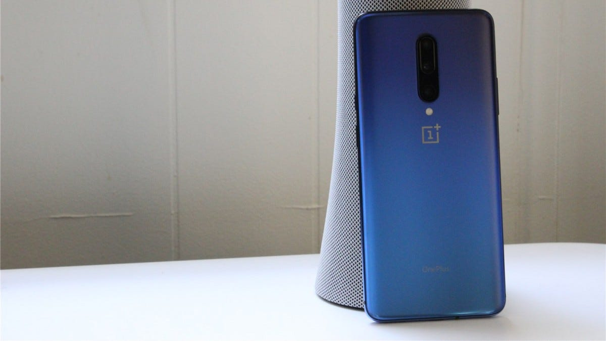 A blue OnePlus 7 Pro phone leaned against a smart speaker.