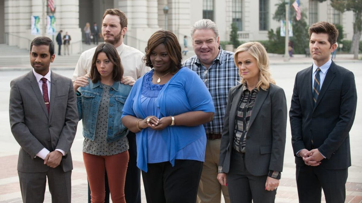 The cast of Parks and Recreation on a sidewalk.
