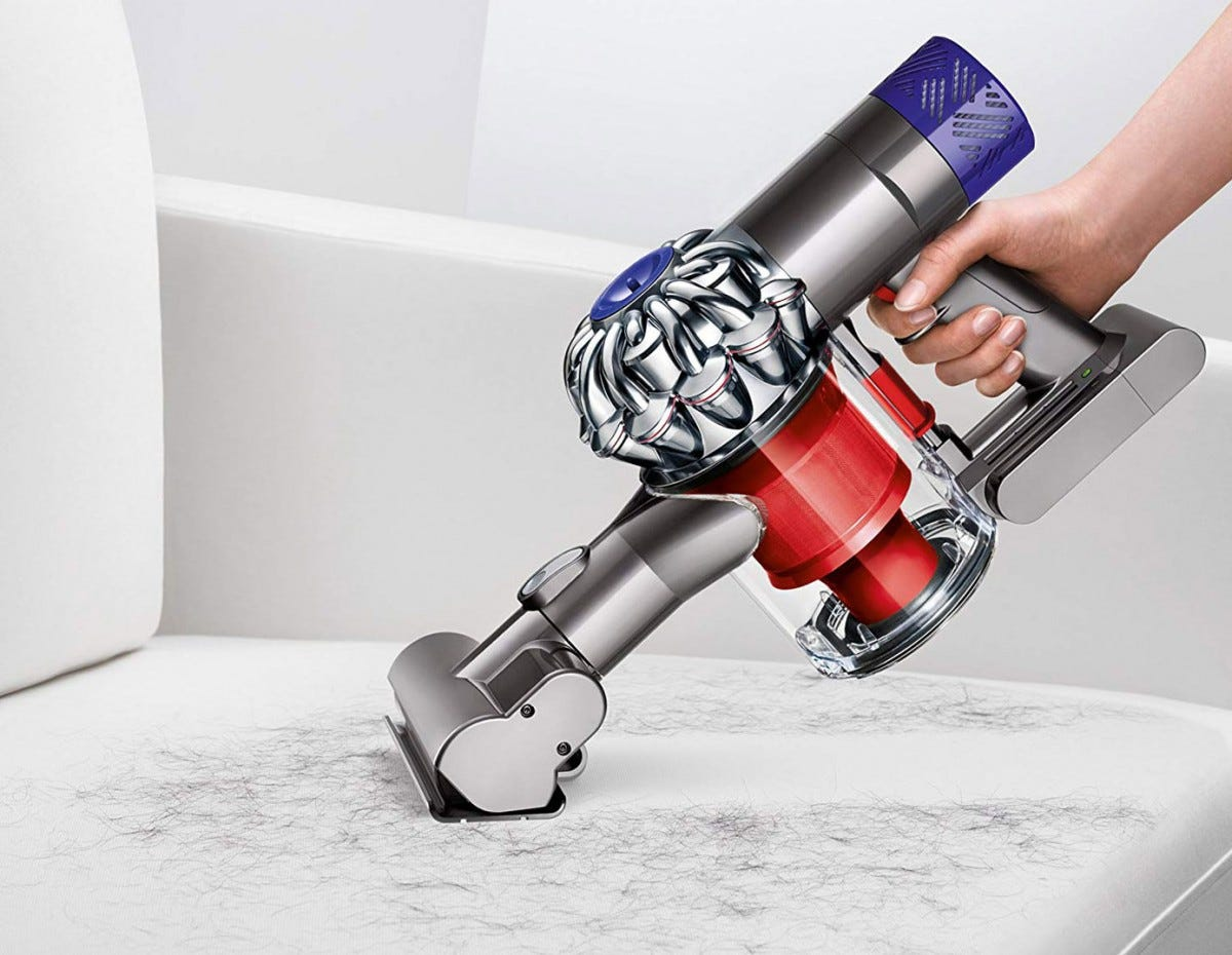 A handheld Dyson vacuum cleaning hair and fur on a chair.
