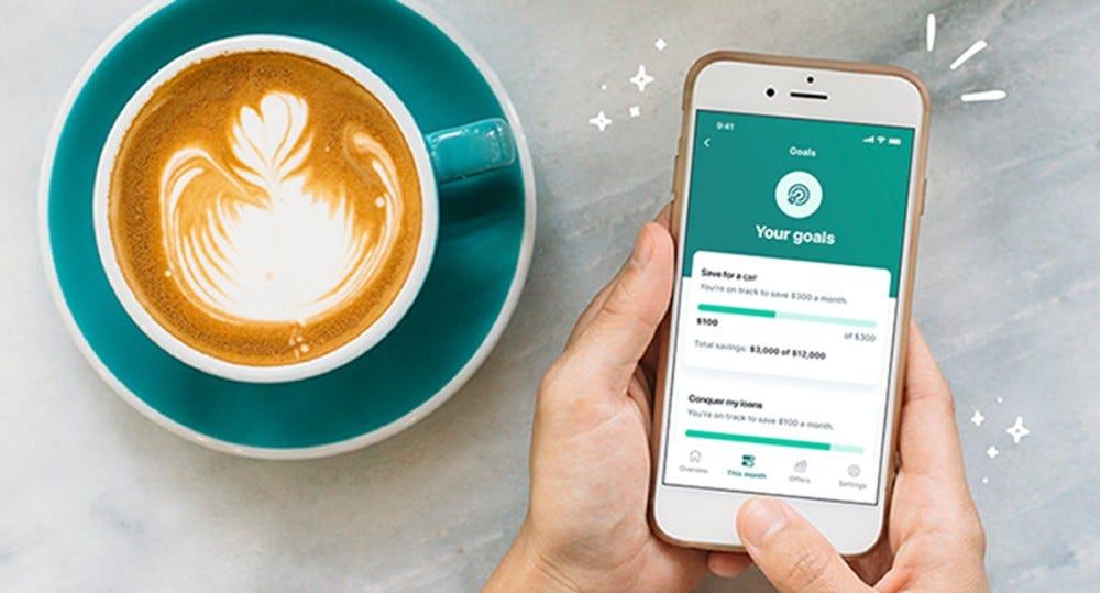A Mint alkalmazás iPhone-on, egy csésze kávé mellett.