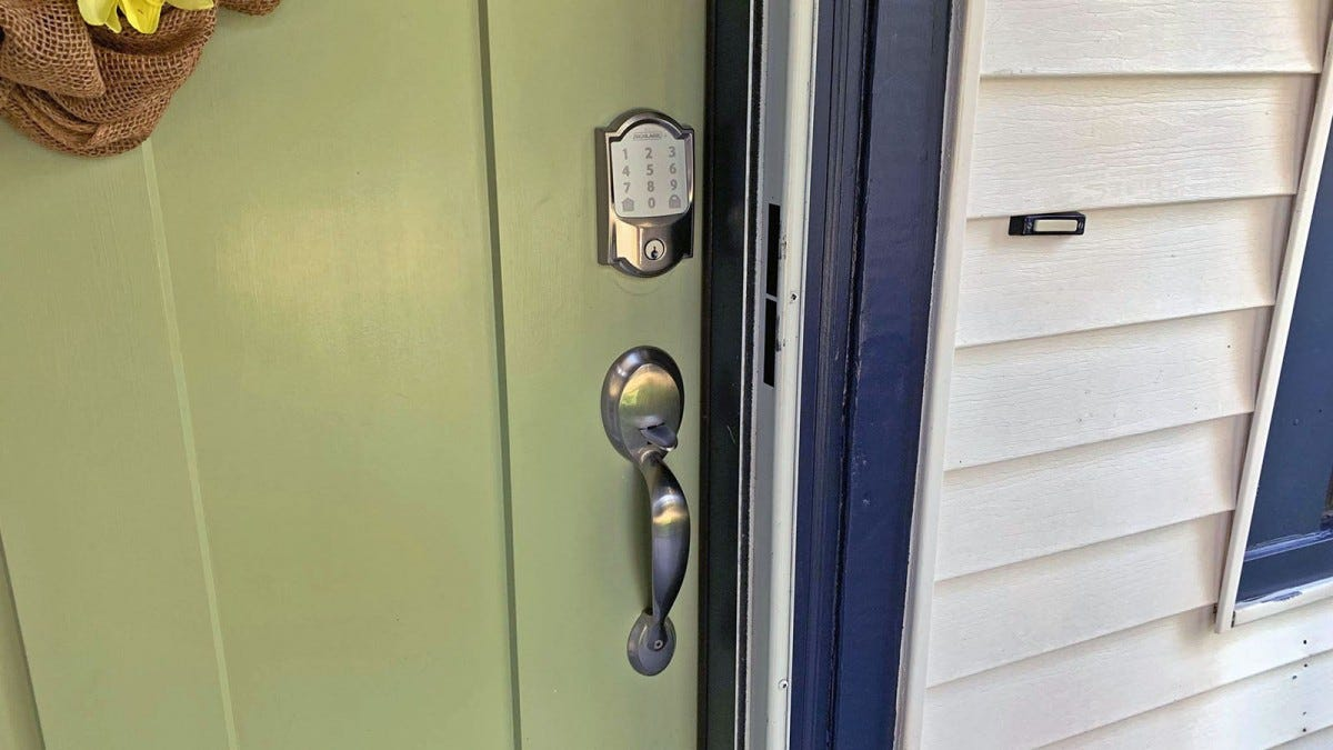 A Schlage Encode lock, above a matching door knob and installed in a olive colored door.
