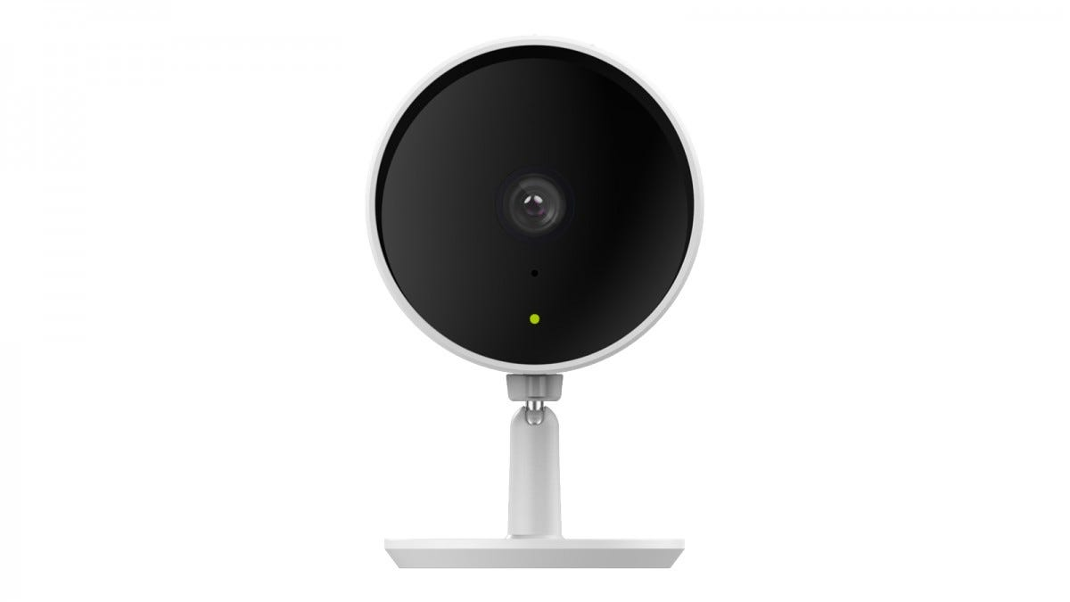 A white security camera with a large black face and green light.