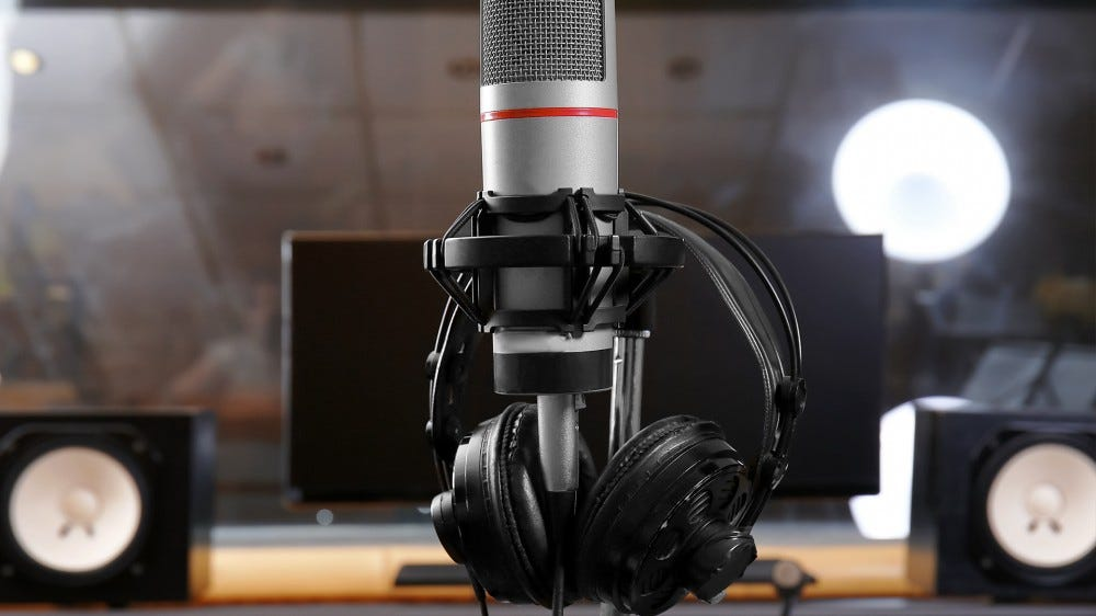 A pair of open-back headphones in a recording studio.