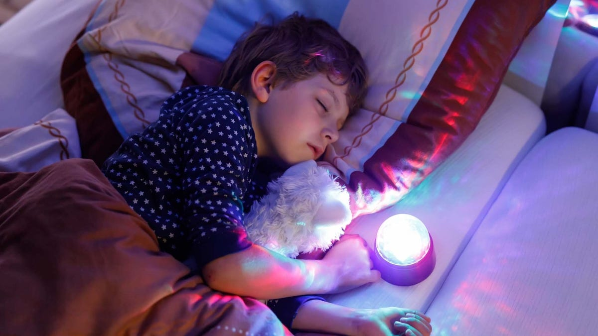Boy sleeping in bed with a projector nightlight nearby