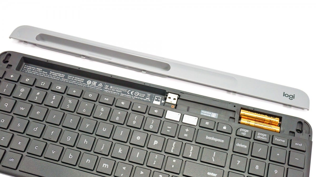 The device tray removed on the Logitech K580 to reveal the battery bay and USB receiver slot.