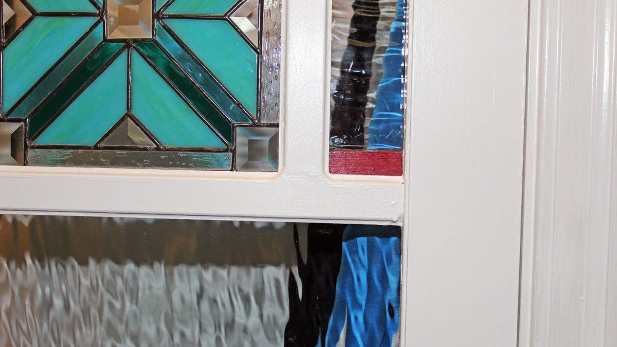 A white door frame encosing stained glass.