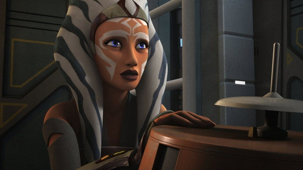 An older Ahsoka looking at an R2 droid.