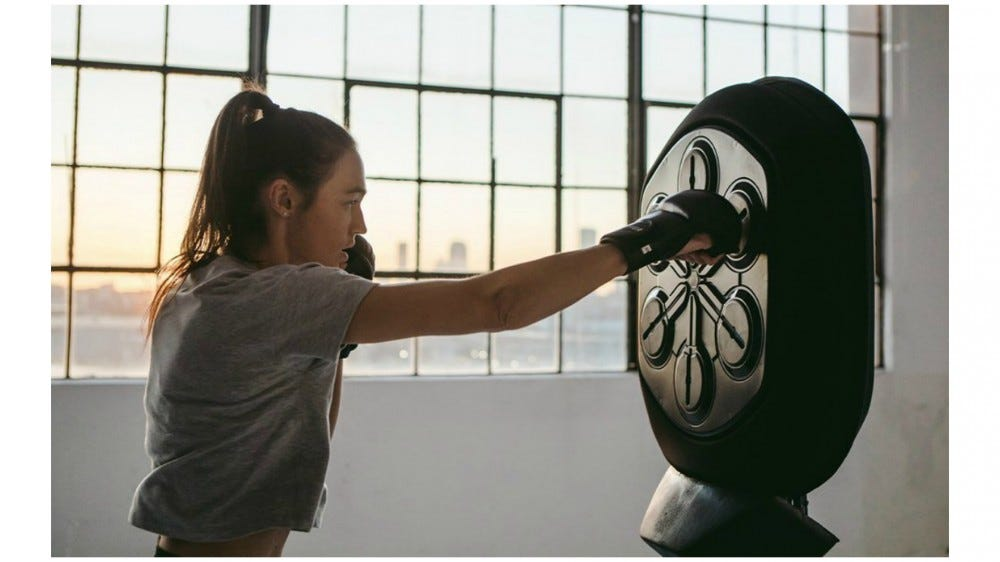 Liteboxer digital rhythmic boxing trainer being hit by a female athlete