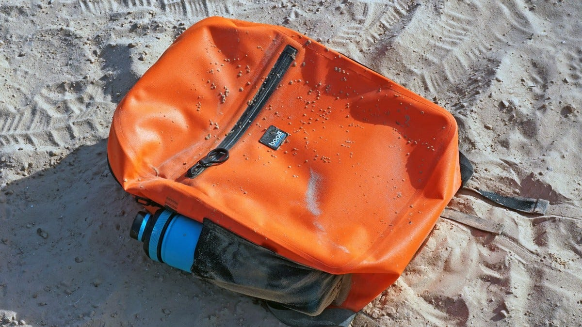 The Hybrid 20 backpack lying in the sand.