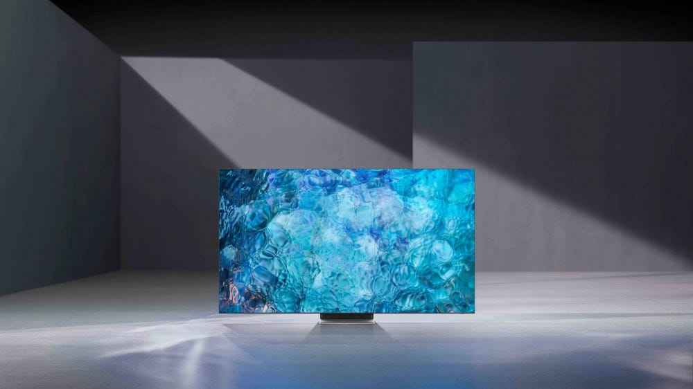 A NEO QLED 8K TV in a dark room, brightly lit.