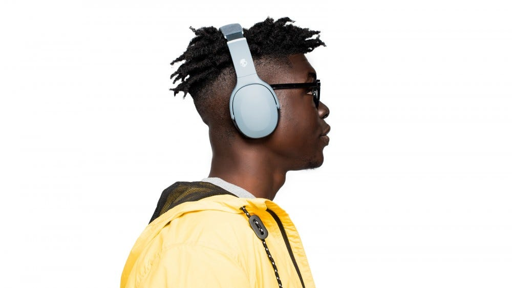 Guy wearing a jacket and the Skullcandy Crusher Evo headphones against a plain background