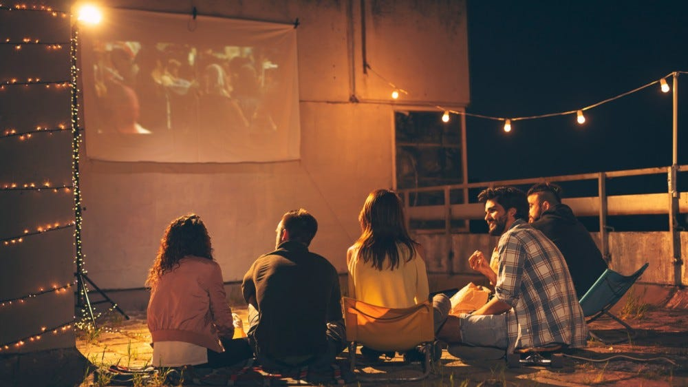 Group of young friends watching a movie on a building rooftop terrace, eating popcorn, drinking, and having fun