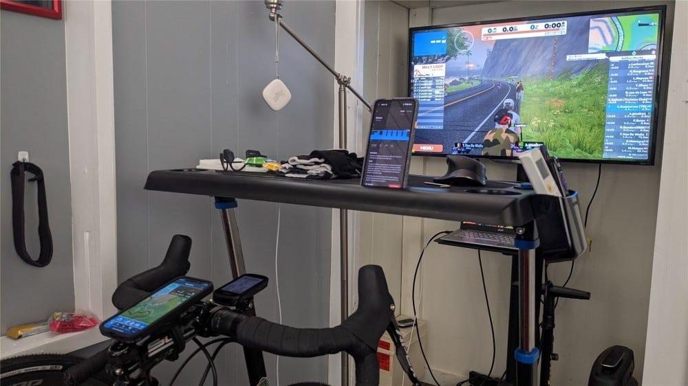 Beltéri edzésbeállítás Zwift segítségével egy TV-n, TrainerRoad telefonon és Gearlock, aki iPhone-t tart a Zwift társalkalmazással.