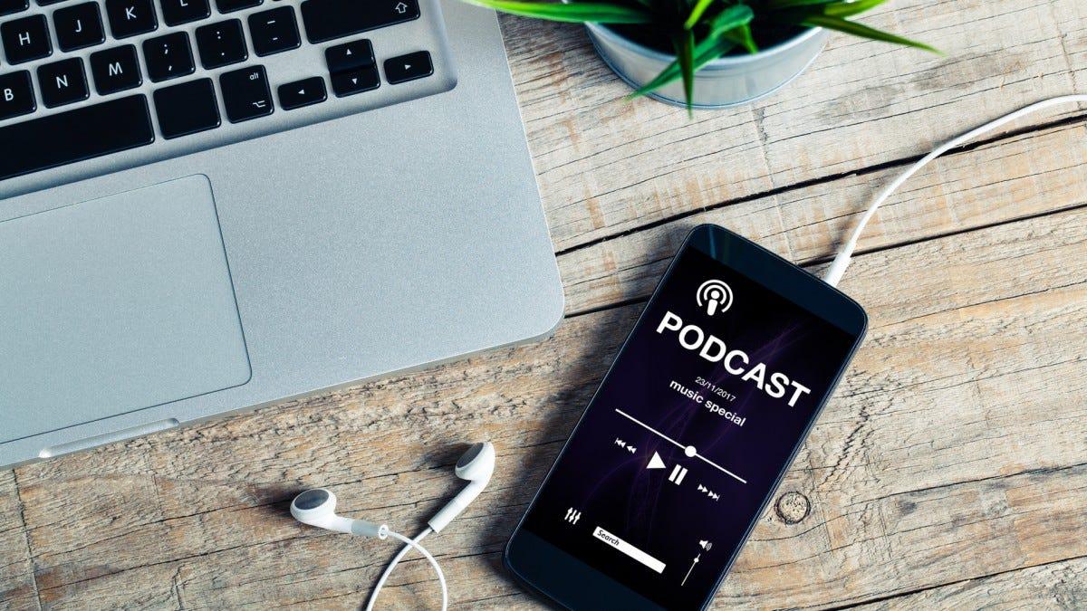 Một podcast chạy trên điện thoại bên cạnh máy tính