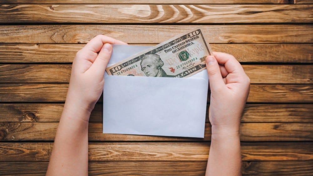 Ten dollar bill being put into an envelope