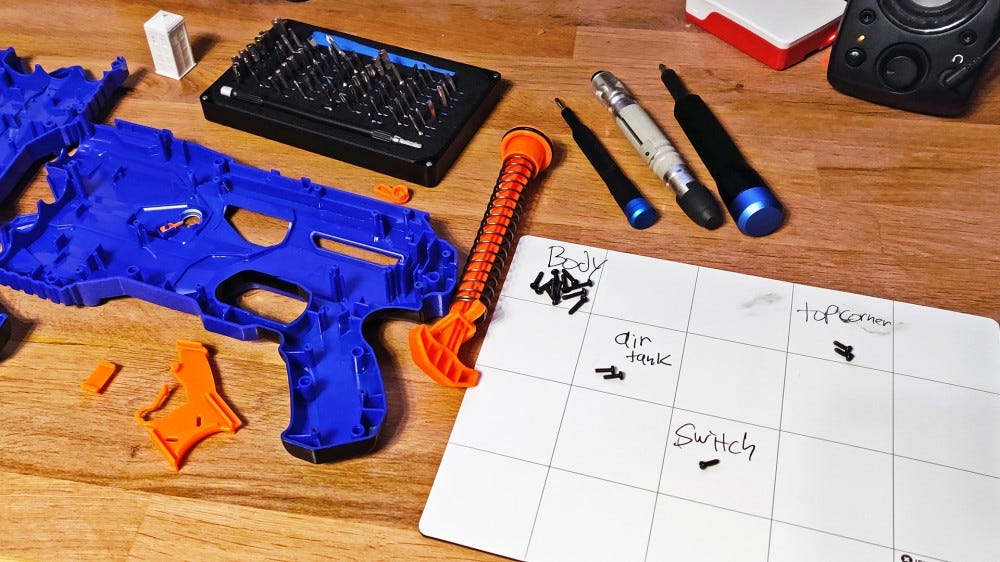 Two iFixit kits surrounded by a torn apart Nerf gun.