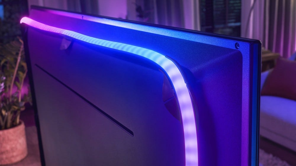 A TV with a colorful lightstrip running along its back.