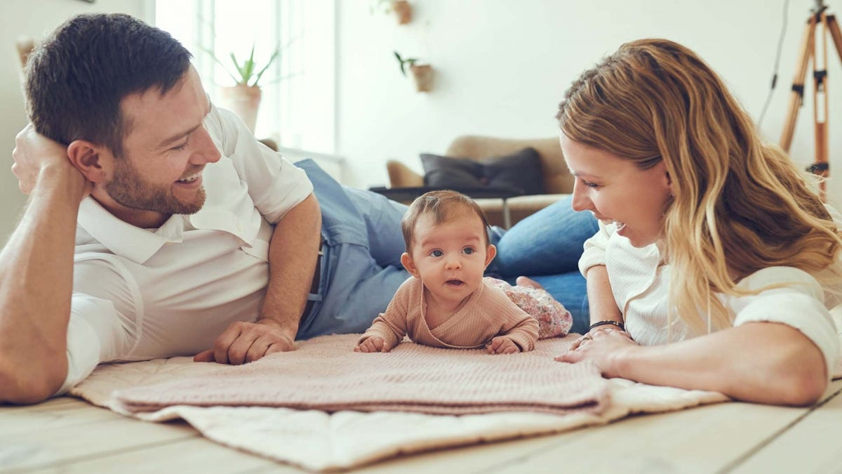 New parents playing with their baby on the floor