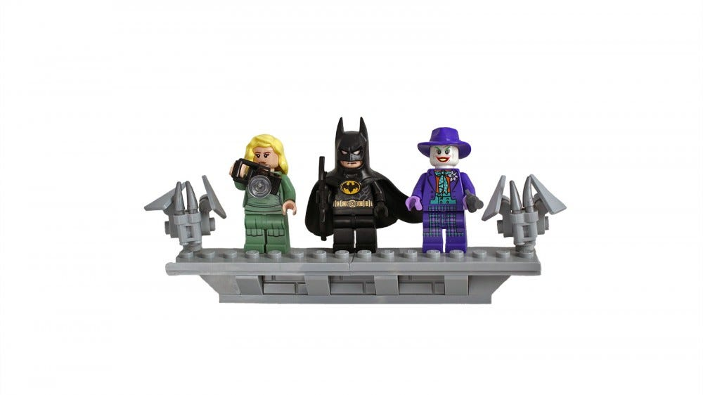 A close up of Vicky Vale, Batman, and Joker in LEGO form standing next to LEGO gargoyles.