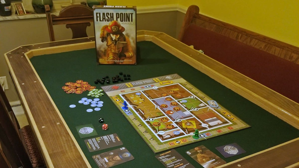 The Flash Point game on a board game table with green felt.