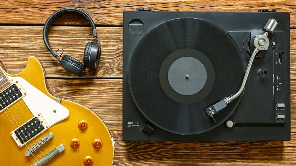 Electric guitar, headphones, and turntable with vinyl on wooden background