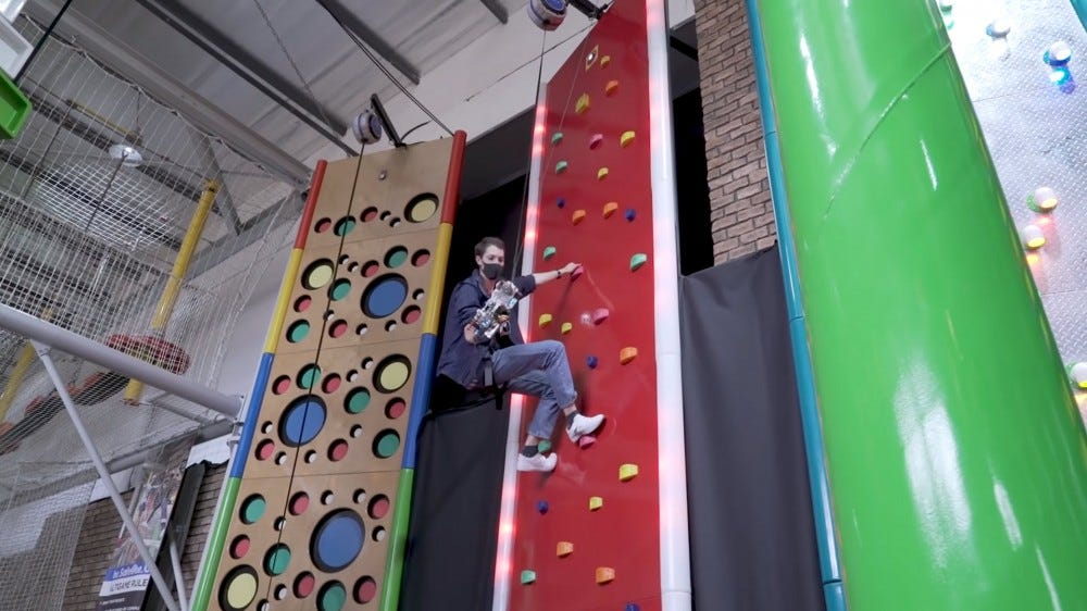 A man high up a rock climbing wall with a grappling hook on his arm.