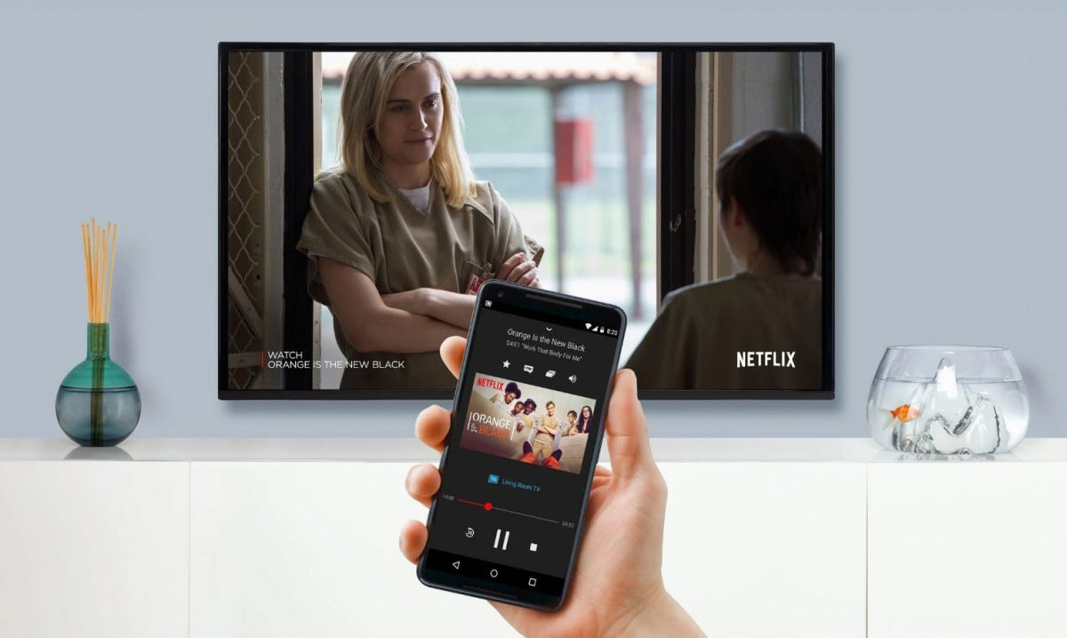 A man's hand holding a phone operating Netflix on a big screen smart TV.