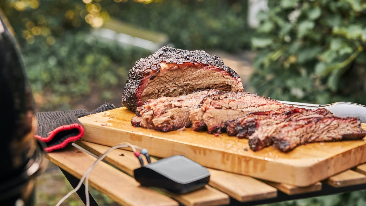 The Weber Connect Smart Grilling hub next to slabs of meat.