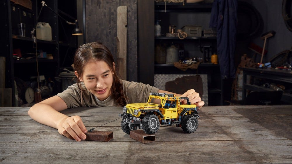 A young child plays with a LEGO Jeep Wrangler on a workbench.
