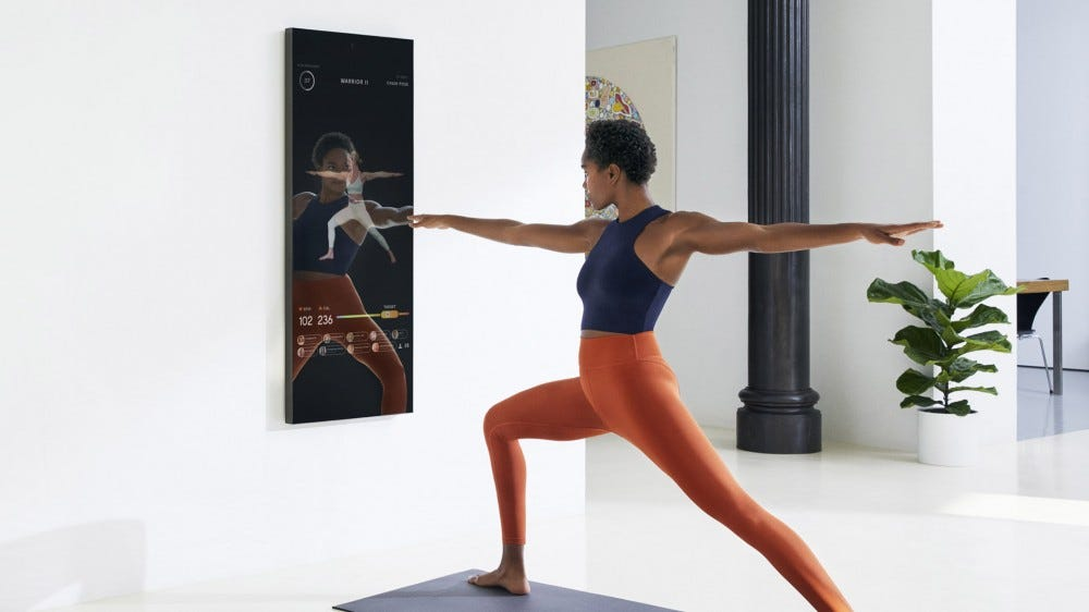 a model poses while using a Mirror digital fitness coach