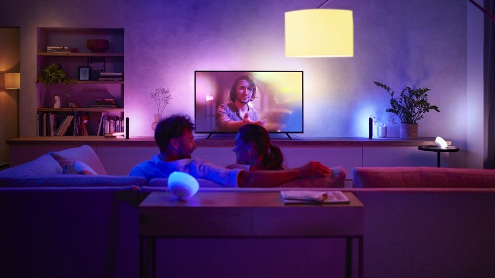 A couple watching TV in a living room surrounded by Philips Hue lights