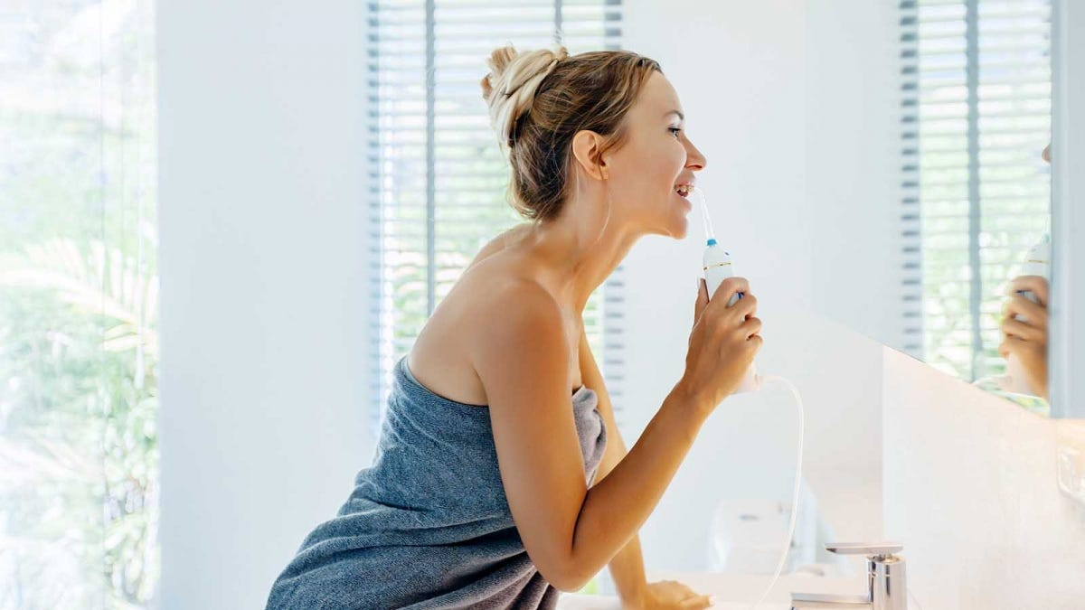 Woman flossing with a water flosser