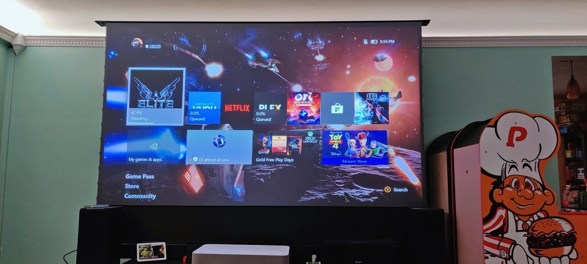 A giant 100-inch screen showing an Xbox home screen in a well-lit room.