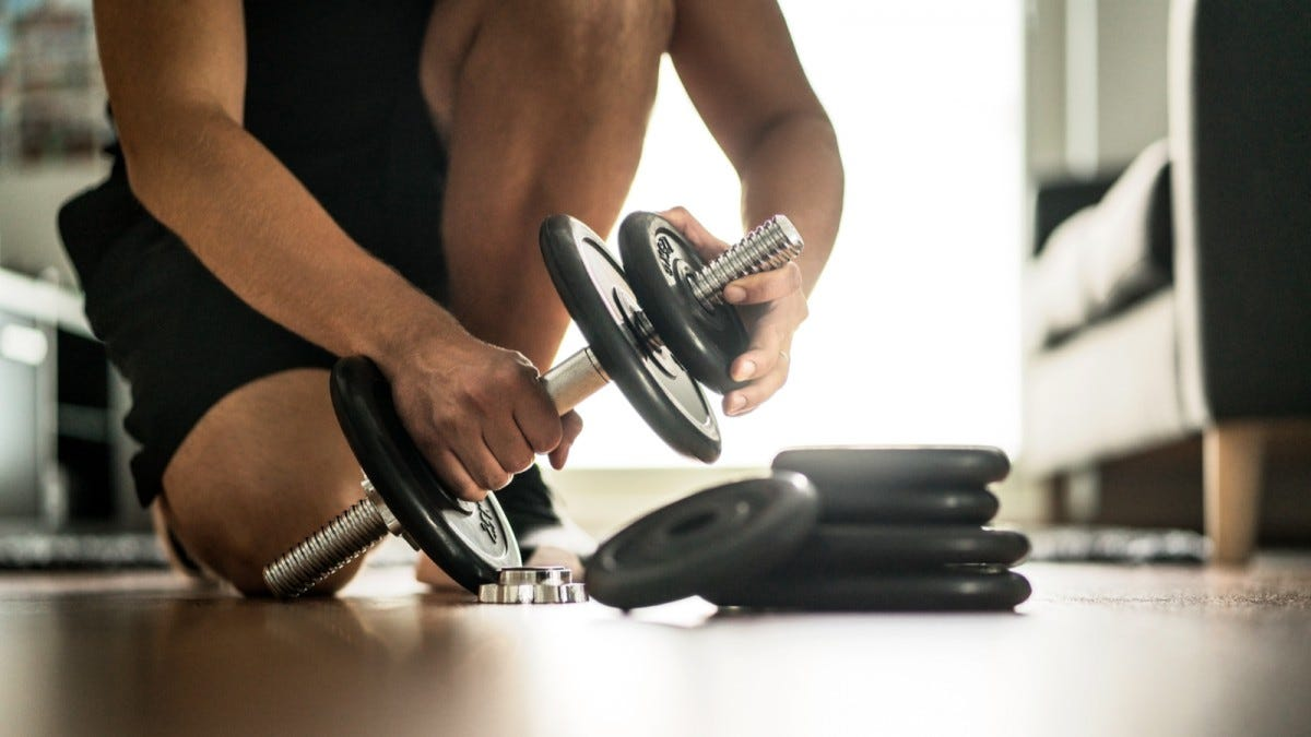 A man's hands changing weights on an adjustable dumbbell set.