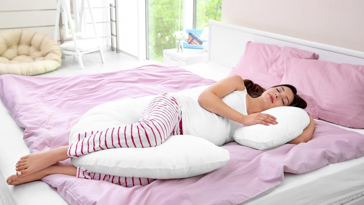 Pregnant woman sleeping with a pregnancy pillow