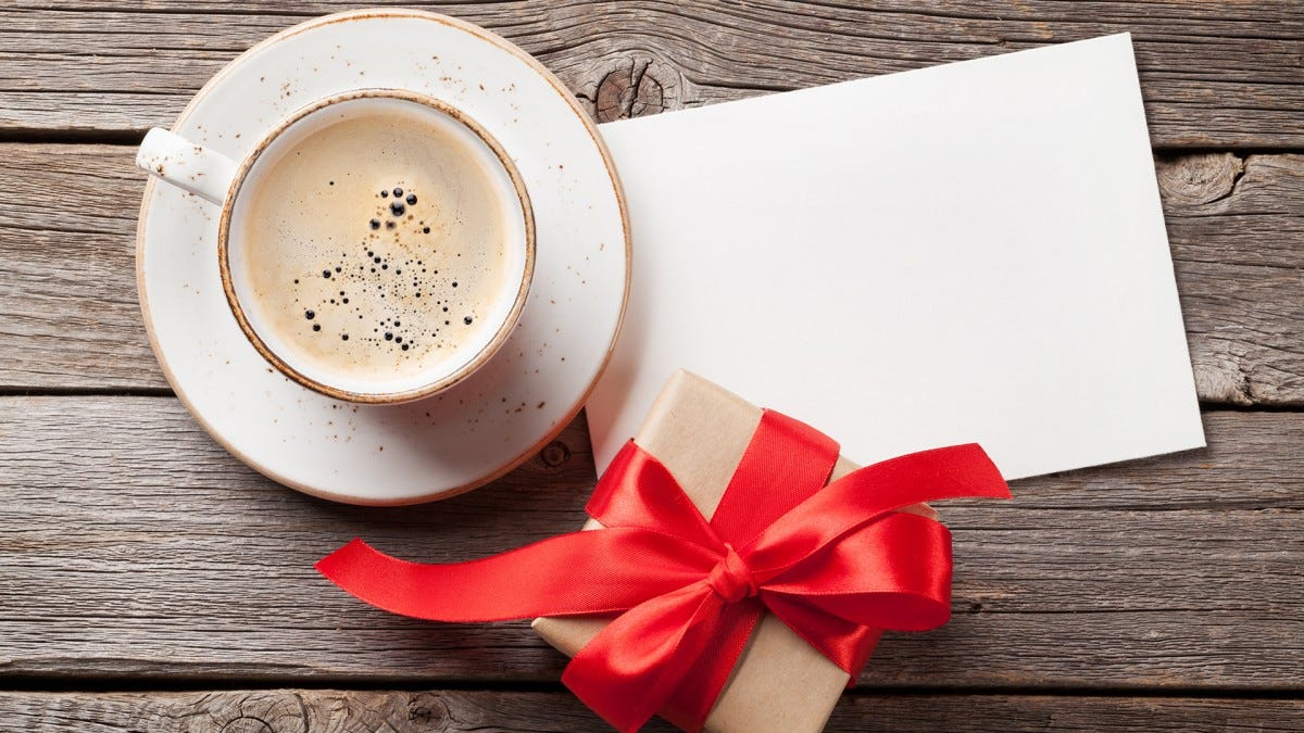 A cup of coffee with a present and an envelope.