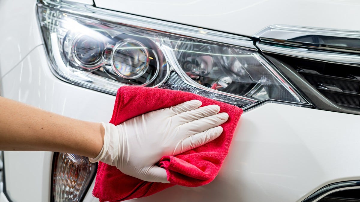 A hand wiping down the exterior of a car.