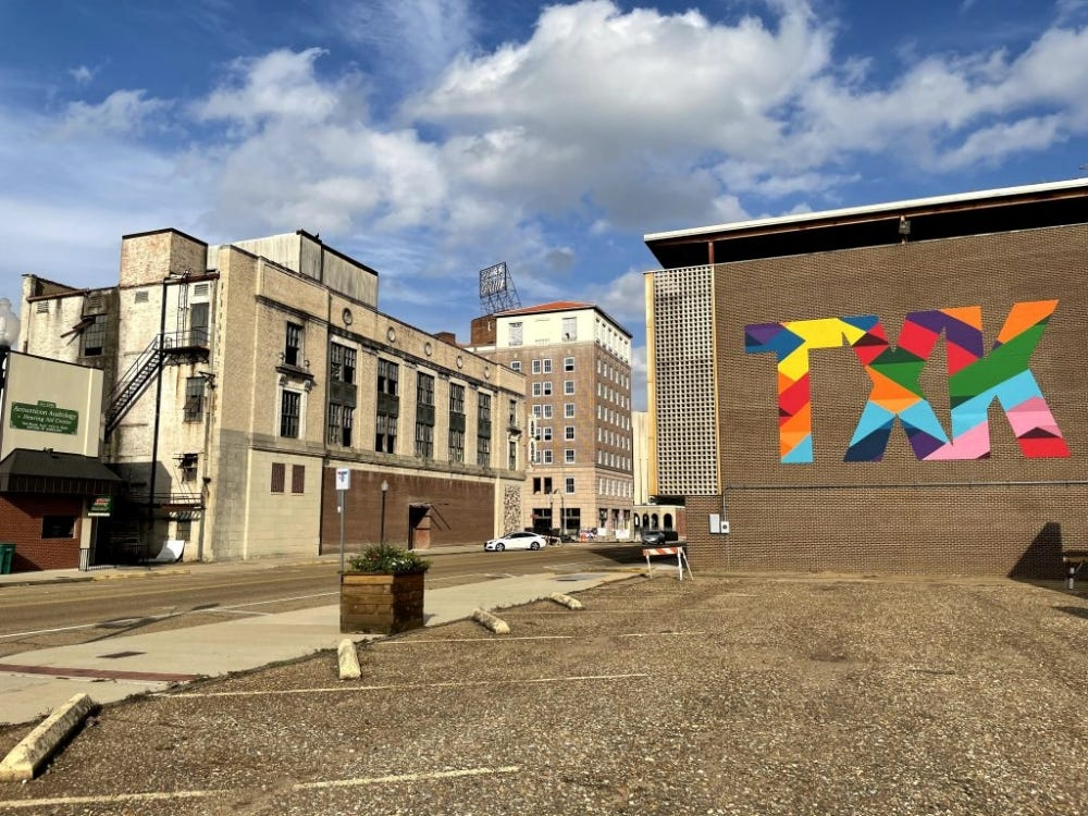 """iPhone 12 Mini Sample: Cityscape shot with old buildings and a colorful """"TXK"""" logo"""