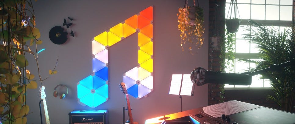 A Nanoleaf panel set in the shape of a musical note hanging on a wall in a music studio.