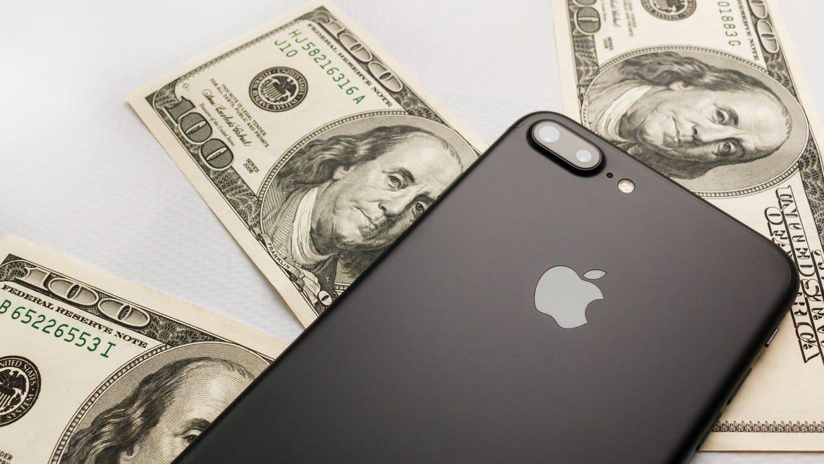 An iPhone X lying on top of three, $100 bills.