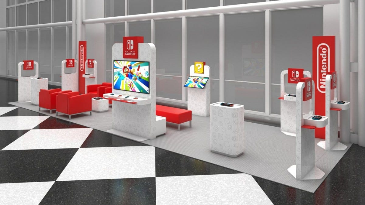 A Nintendo pop up lounge, decked and red, grey and filled with Nintendo switches.