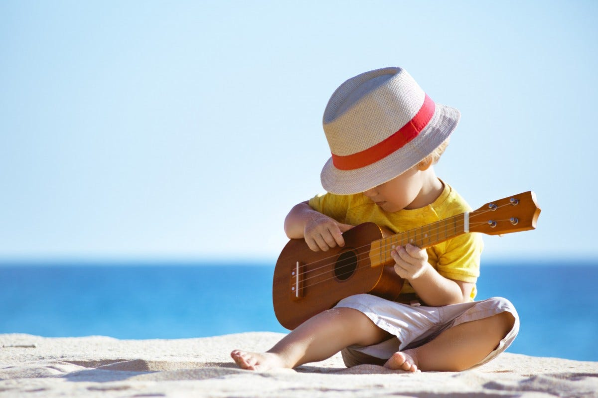 A young boy playing Ukulele on the beach.