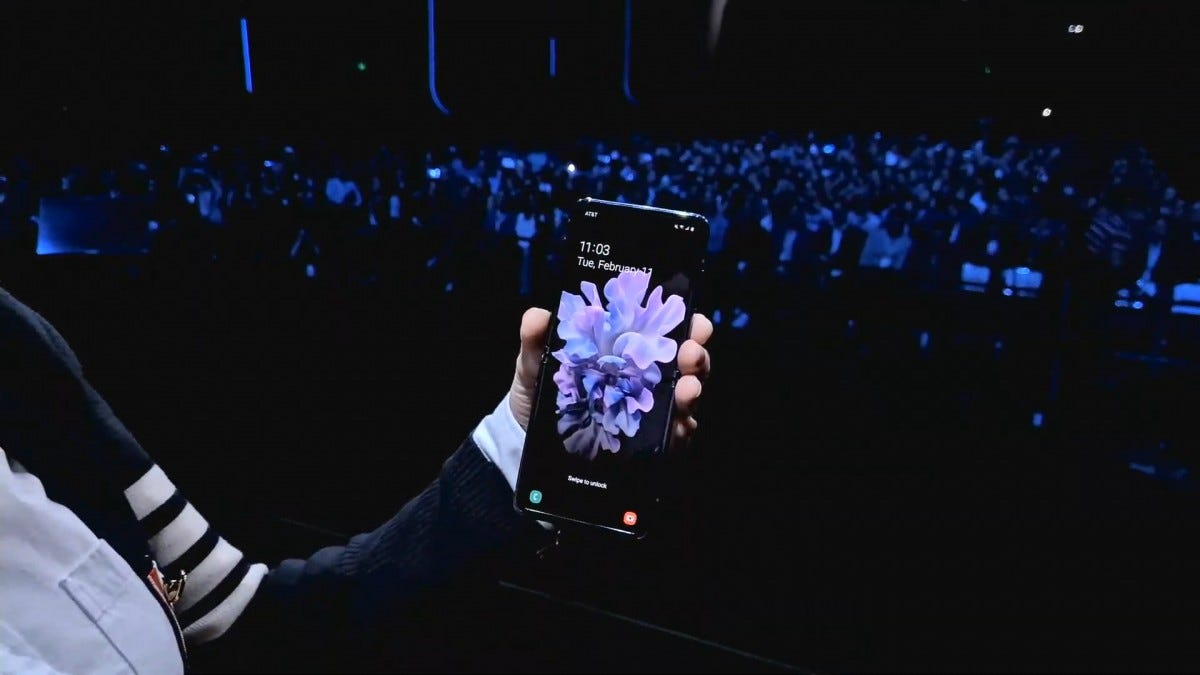 A person holding the Galaxy Z Flip completely open with a flower on the display.