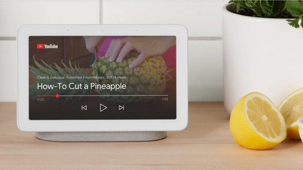 Google Nest Hub smart display with YouTube video display on the kitchen counter next to lemons