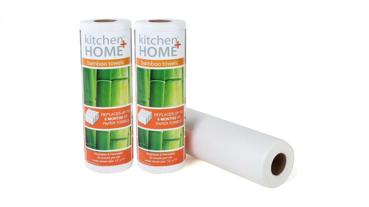 Two rolls of Kitchen + Home Bamboo Towels in their packaging, and one roll out of its package lying next to them.