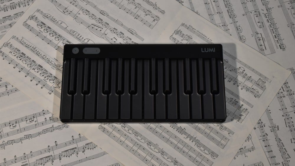 LUMI Keys powered off against sheet music background