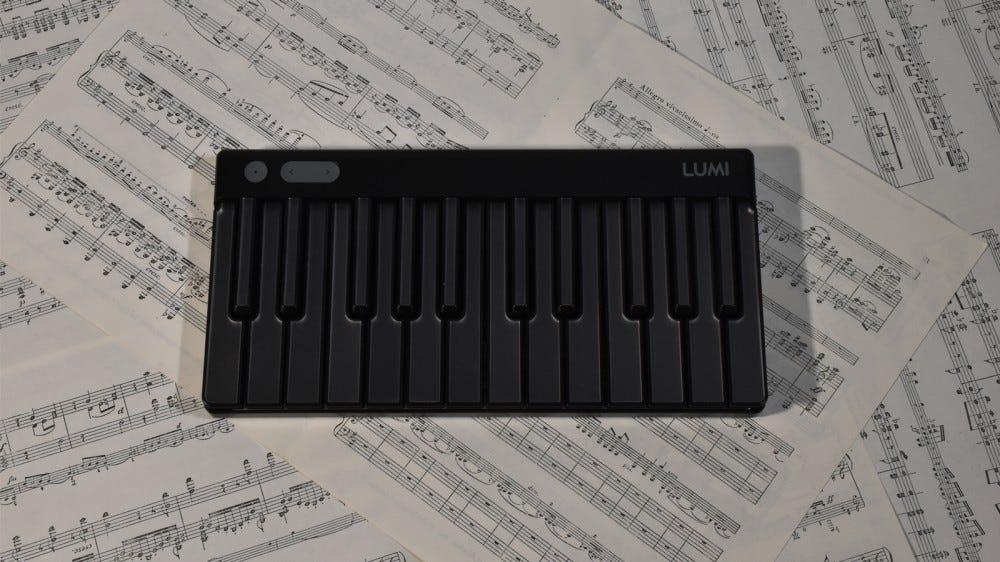 LUMI Keys powered off against sheet music background